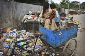 In this photo taken Tuesday, Nov. 17, 2009, children play in a rickshaw at a garbage dump in Hyderabad, India. Twenty years after the U.N. adopted a treaty guaranteeing children's rights, fewer youngsters are dying and more are going to school, but an estimated 1 billion still lack services essential to their survival and development, UNICEF said Thursday. (AP Photo/ Mahesh Kumar A.)
